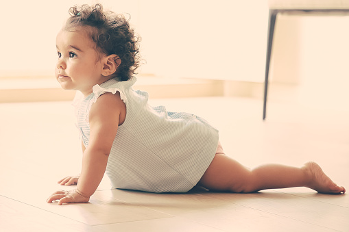 Adorable dark curly haired baby girl wearing pale blue cloth, crawling on floor at home, looking away. Kid at home and childhood concept