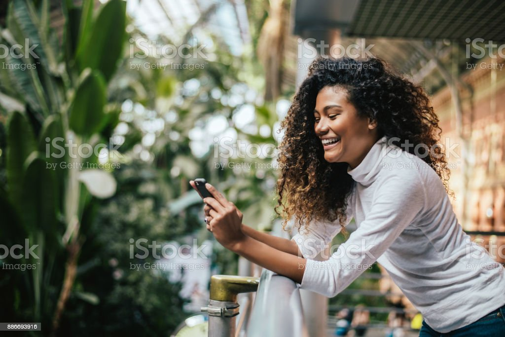 Adorable dark skinned woman with afro hairstyle using her phone. stock photo