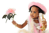 Close-up of an adorable two year old diva in pearls, a pink hat, boas and holding a flower while talking on a fancy French phone.  On a white background.
