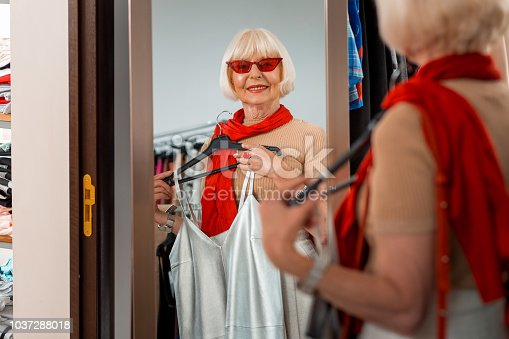 istock Adorable elderly woman being reflected in shopping mirror 1037288018