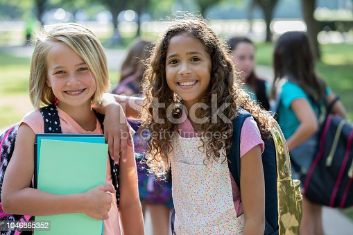 Caucasian and African American girls are smiling and looking at the camera while waiting outside school together. Students are wearing backpacks and holding homework assignments,