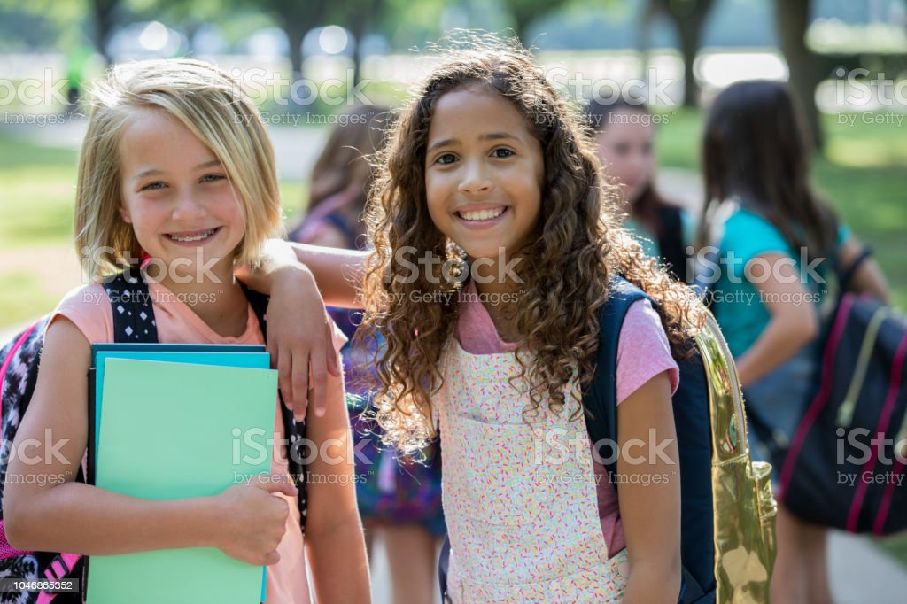 Adorable elementary age best friends wait outside school stock photo