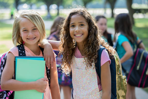Adorable elementary age best friends wait outside school Caucasian and African American girls are smiling and looking at the camera while waiting outside school together. Students are wearing backpacks and holding homework assignments, field trip stock pictures, royalty-free photos & images