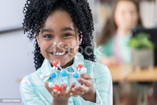 istock Adorable elementary student showing molecular structure model 695655868