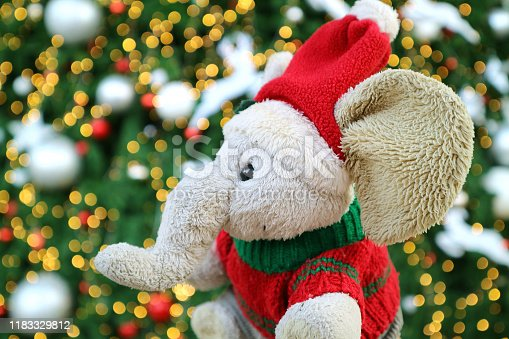 Adorable Elephant doll with Santa Hat in front of Glittering Christmas Tree