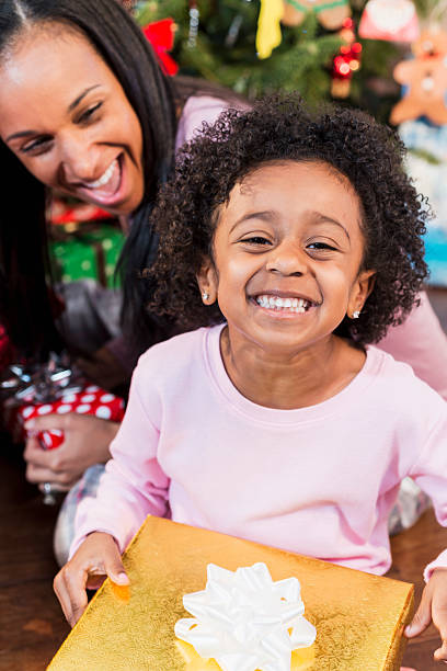 adorable, excited african american child with parent holding christmas present - little girls giving head stock photos and pictures