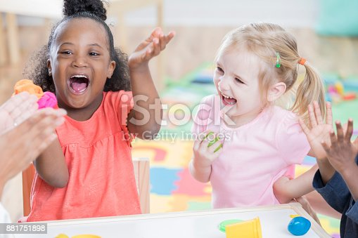 istock Adorable excited preschool girls at school 881751898