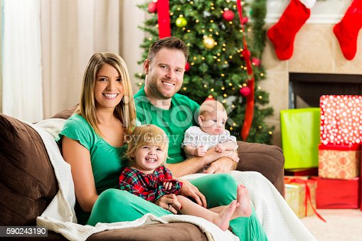579124316 istock photo Adorable family poses for photo on Christmas morning 590243190