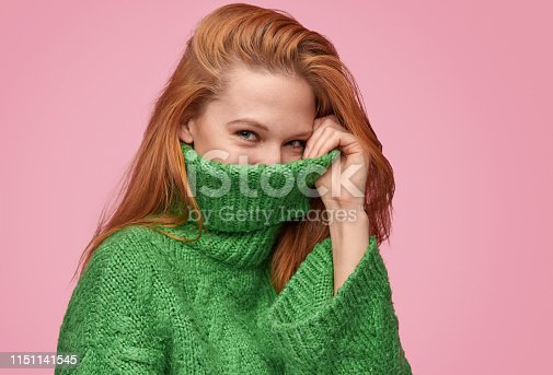 Young redhead woman hiding face in neck of warm green sweater looking at camera on pink backdrop