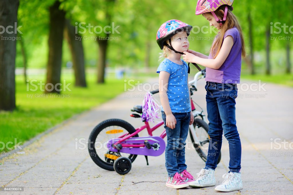 Adorable girl helping her sister to put a bicycle helmet on stock photo