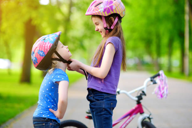 Adorable girl helping her sister to put a bicycle helmet on - foto stock