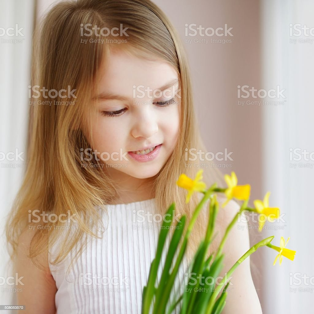 Adorable girl holding daffodils by the window stock photo