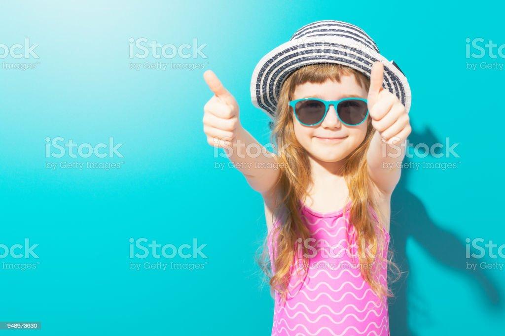 Adorable chica en traje de baño mostrando los pulgares para arriba foto de stock libre de derechos