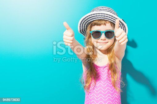 istock Adorable girl in swimsuit showing thumbs up 948973630