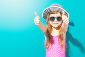 Little happy girl in beach outfit with hat and sunglasses holding thumbs up on blue background.