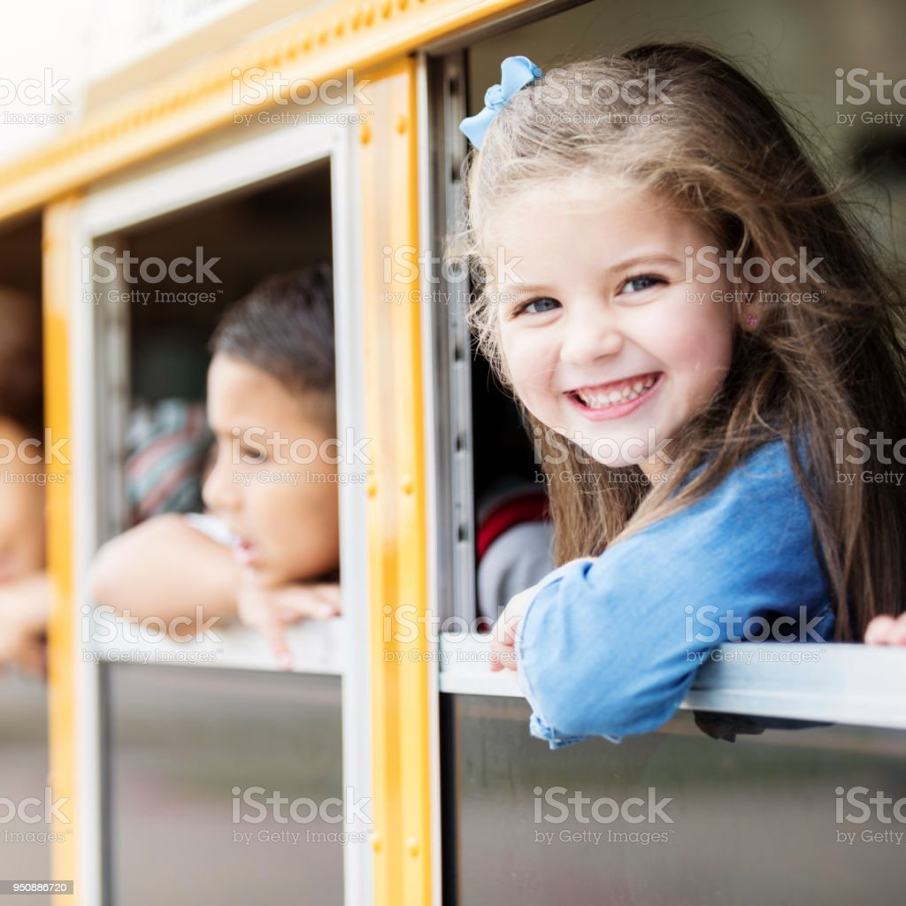 Adorable girl looks out of school bus window stock photo
