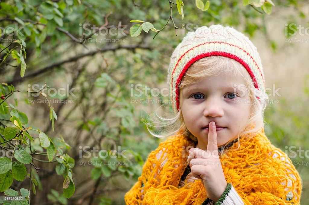 adorable girl making silence sign stock photo