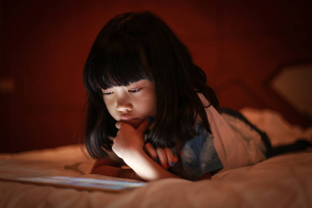 Adorable girl playing on a digital tablet. stock photo