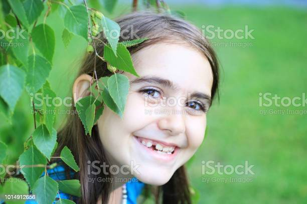 Photo of Adorable girl smilign and peaking through the leaves