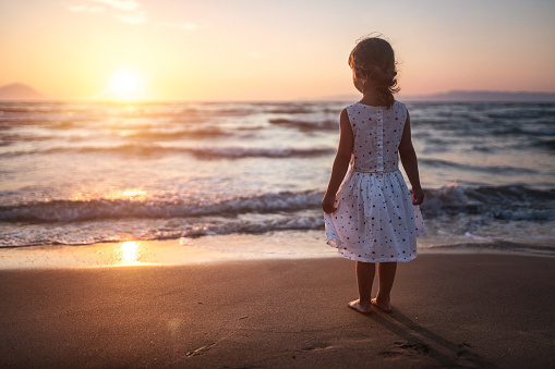 Adorable girl watching sunset standing at sandy beach near sea