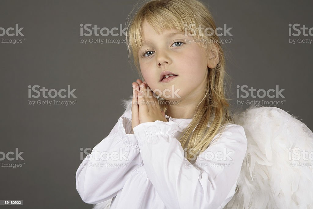 adorable girl with angel wings in amen gesture royalty-free stock photo