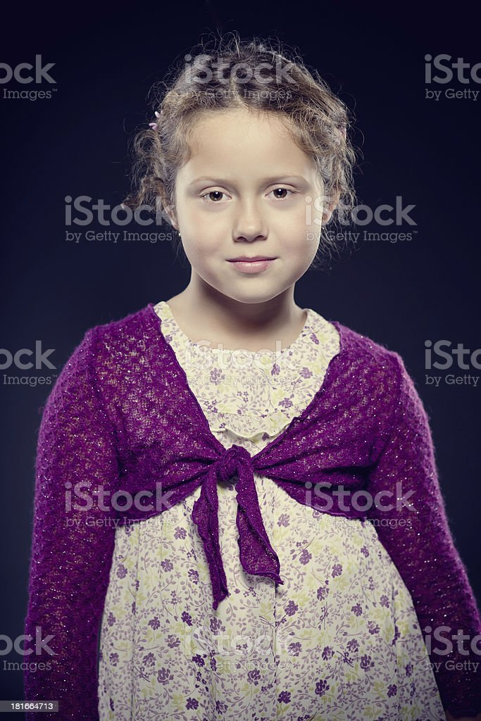 Adorable girl with curly hair posing in a studio royalty-free stock photo
