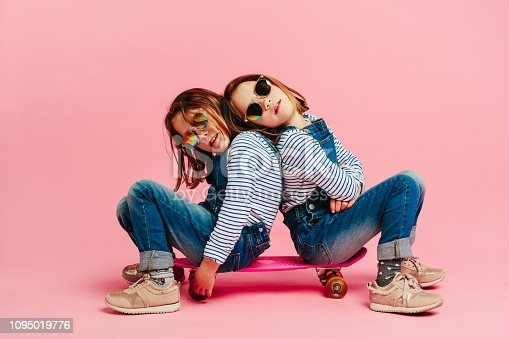 istock Adorable girls sitting together on a skateboard 1095019776
