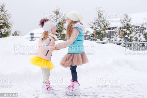 Adorable girls skating on ice rink outdoors in winter snow day picture id1084124378?b=1&k=6&m=1084124378&s=612x612&h=ea0jlxuaa tppt7gptkzsuh6oo uza0f k6rdoto8ok=