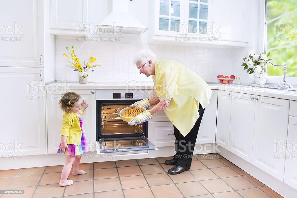 Adorable granddaughter with her pretty great grandmother baking apple pie stock photo