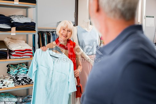 istock Adorable grey haired woman accepting compliments from salesman concerning her chosen dress 1037288418