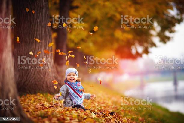 Adorable happy baby girl throwing the fallen leaves up playing in the picture id858123352?b=1&k=6&m=858123352&s=612x612&h= hjshmfaavs0wt zcj  ycwaufp13nicv0 gg6wdtii=