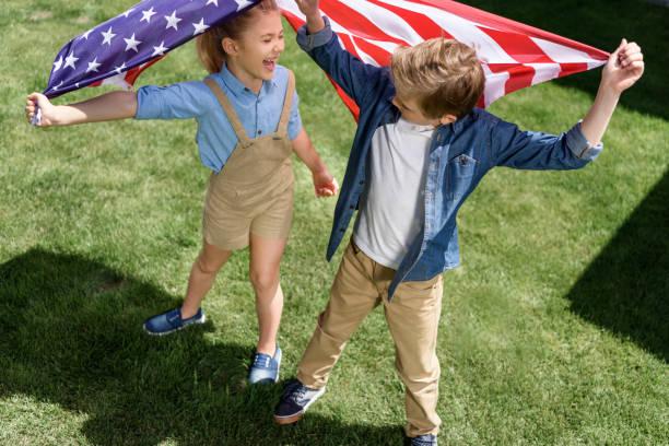 adorable happy brother and sister waving american flag, celebrating 4th july - independence day - family 4th of july zdjęcia i obrazy z banku zdjęć