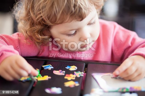 istock Adorable happy little child playing with puzzle. 916914248