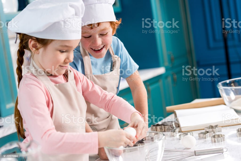 adorable happy little kids in chef hats and aprons making dough together in kitchen stock photo