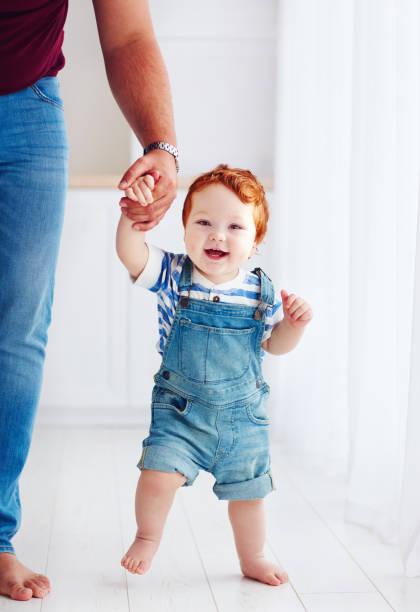 entzückende glücklich kleinkind jungen gehen mit der hilfe des vaters - jeans overall stock-fotos und bilder