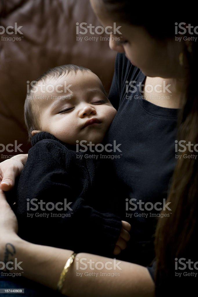 Adorable Hispanic Baby Boy Sleeping in Arms of Mother stock photo
