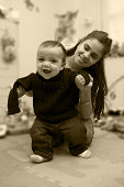 istock Adorable Hispanic Baby Boy Walking with Mother in Playroom, Sepia 174639525