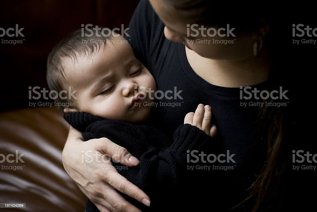 Adorable Hispanic Baby Sleeping in Arms of Mother, Copy Space stock photo