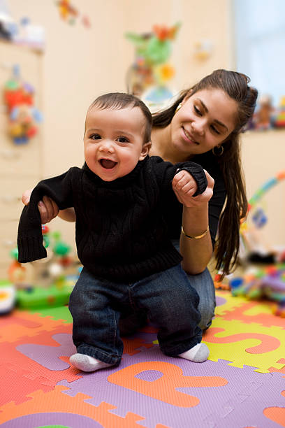 Adorable Hispanic Baby Taking First Steps with Mother in Playroom stock photo