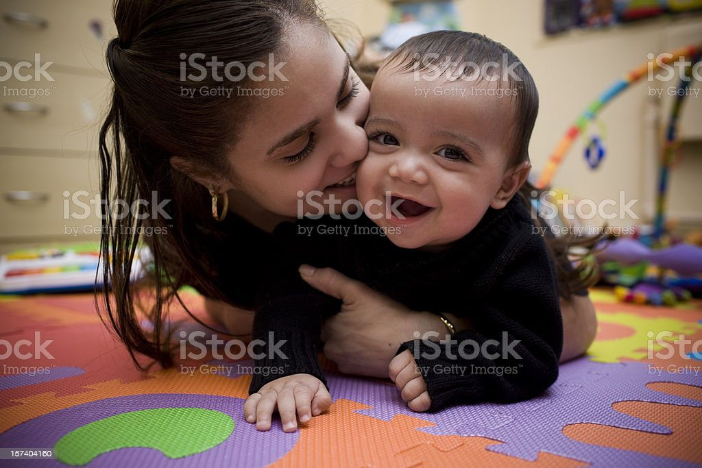 Adorable Hispanic Young Mother and Son in Home Playroom stock photo