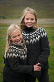 Icelandic girls, adorable young blonde-haired sisters, wearing matching traditional woolen sweaters, Fluguyri horse farm, Skagafjordur, Iceland, Europe