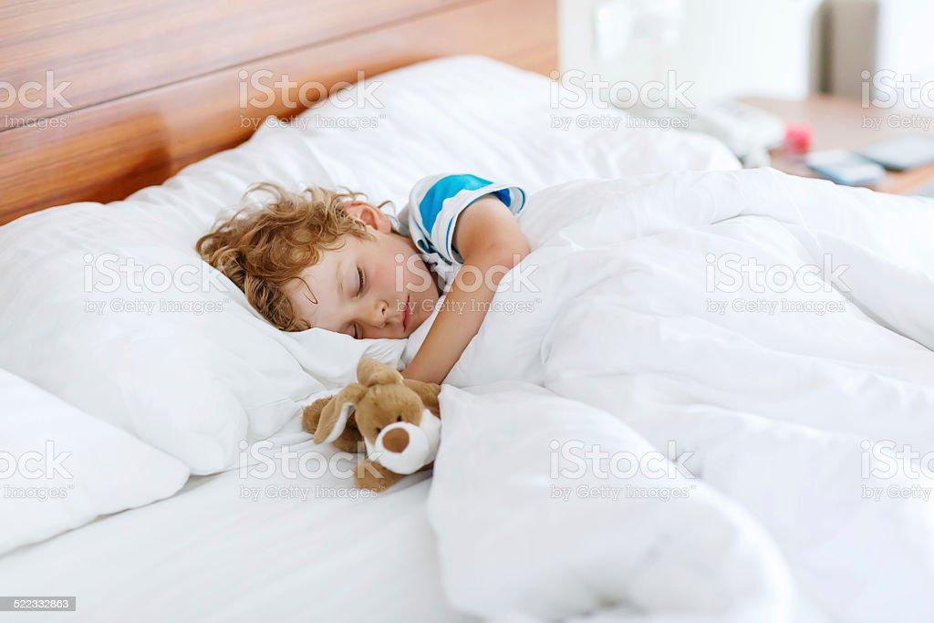 Niedliche Kind junge nach einer Nacht in weißen Bett mit Spielzeug – Foto