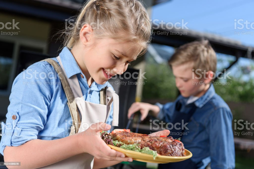 adorable kid girl holding plate with fresh cooked steaks while her brother preparing meat on grill stock photo