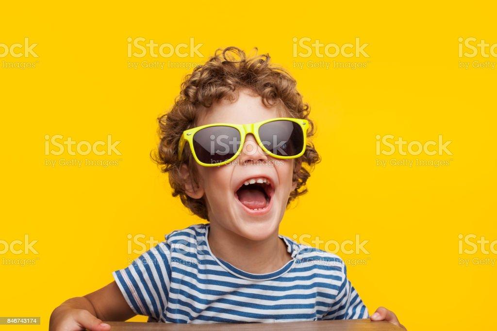 Adorable niño en gafas de sol brillantes naranja foto de stock libre de derechos