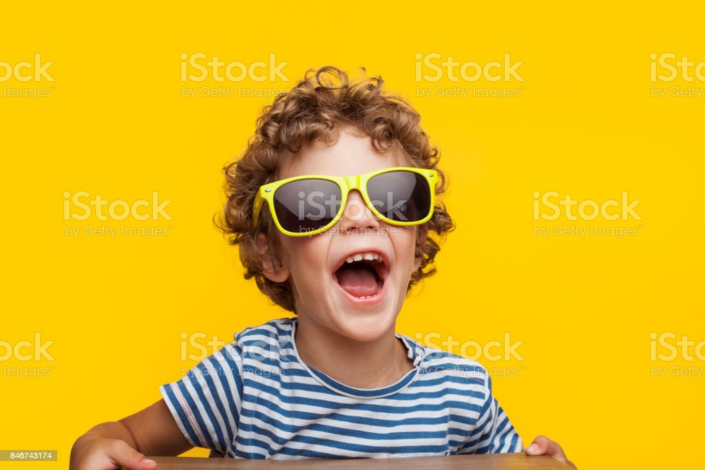 Adorable kid in bright sunglasses on orange stock photo