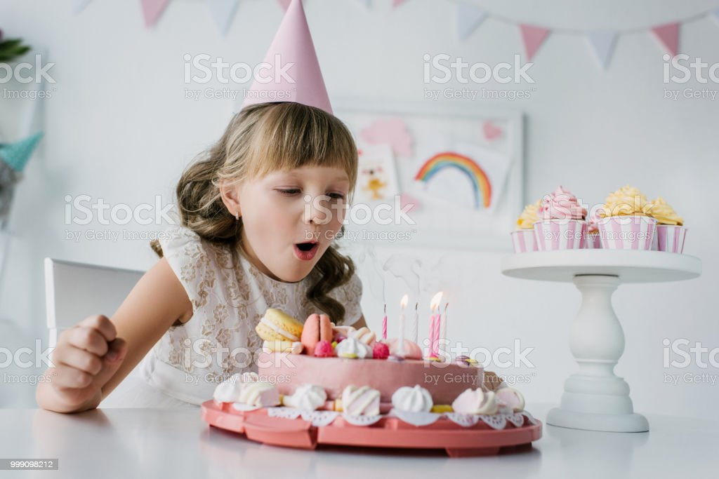 Adorable Kid In Cone Blowing Out Candles From Birthday Cake On Table