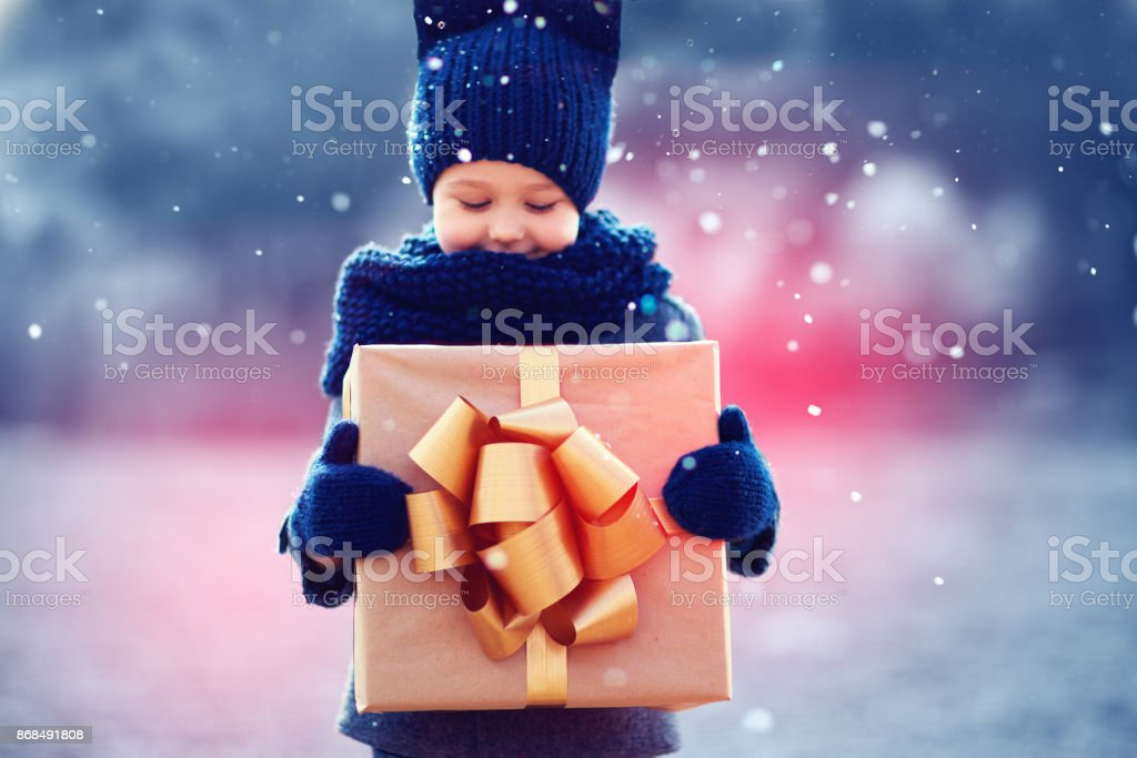 adorable kid with big gift box under a snowfall. Focus on gift box stock photo