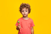 Charming curly boy looking at camera while holding lollipop on orange background.