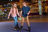 adorable kids holding hands while skating together on roller rink