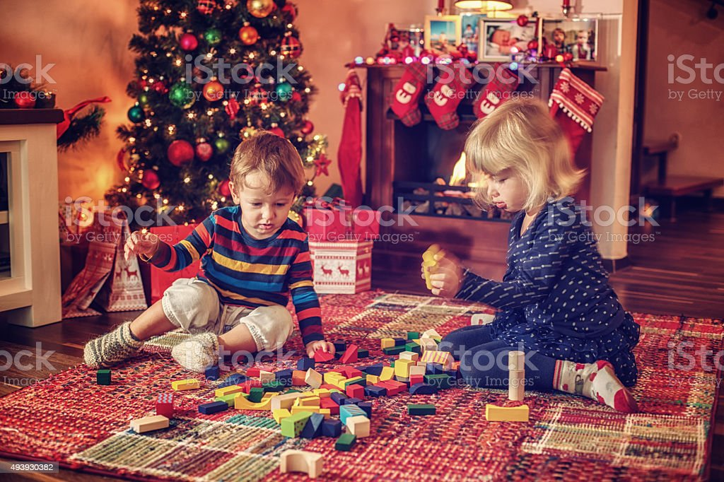 Adorable Kids Playing in in front of Christmas Tree stock photo